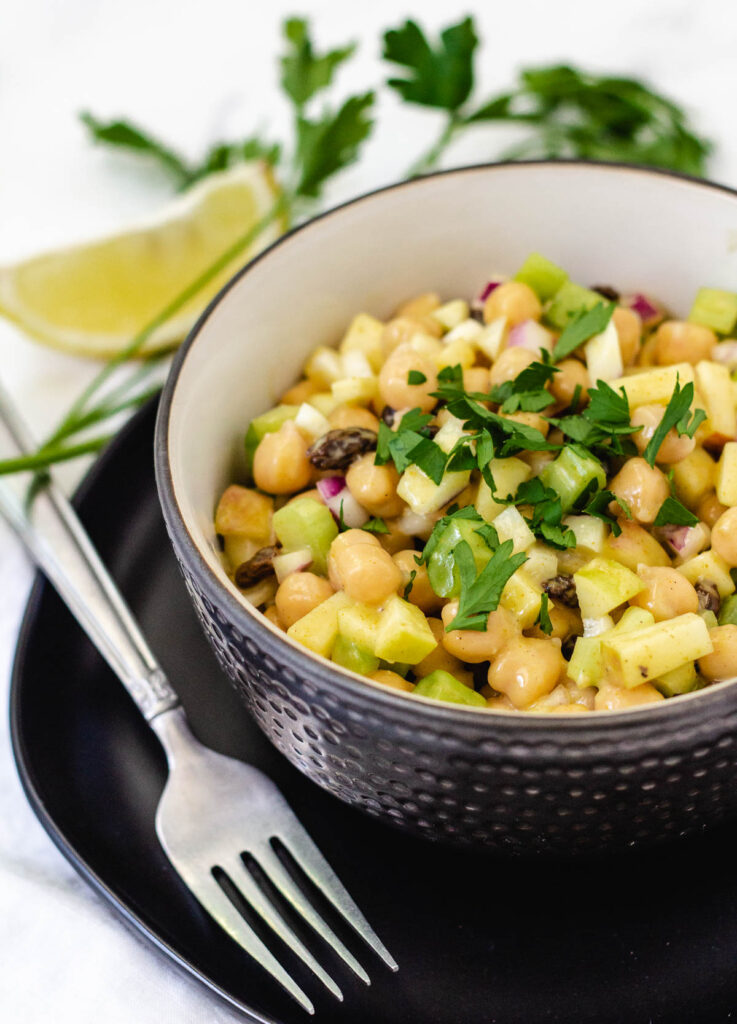 Chickpea curry salad in a bowl on top of a black plate topped with parsley with fork on the side.