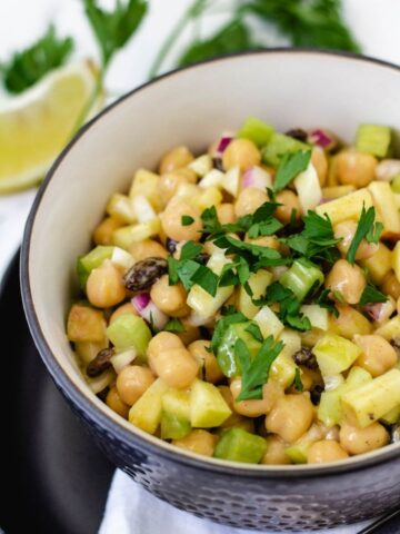 Chickpea curry salad topped with parsley in bowl.