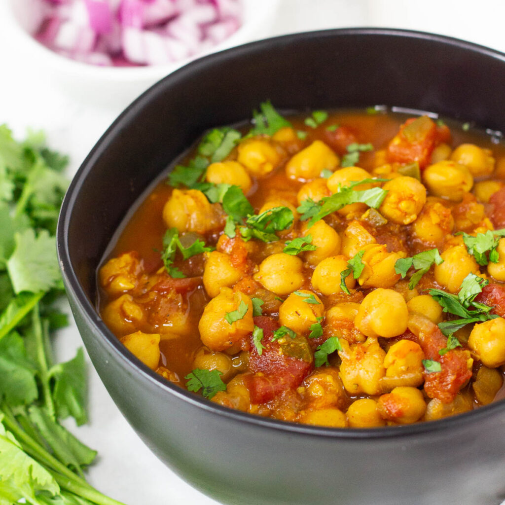 Chana masala topped with cilantro in black bowl.