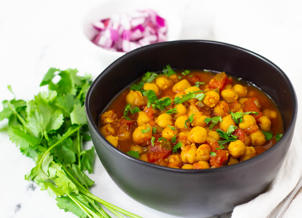 Bowl of cooked chana masala beside a bunch of cilantro.