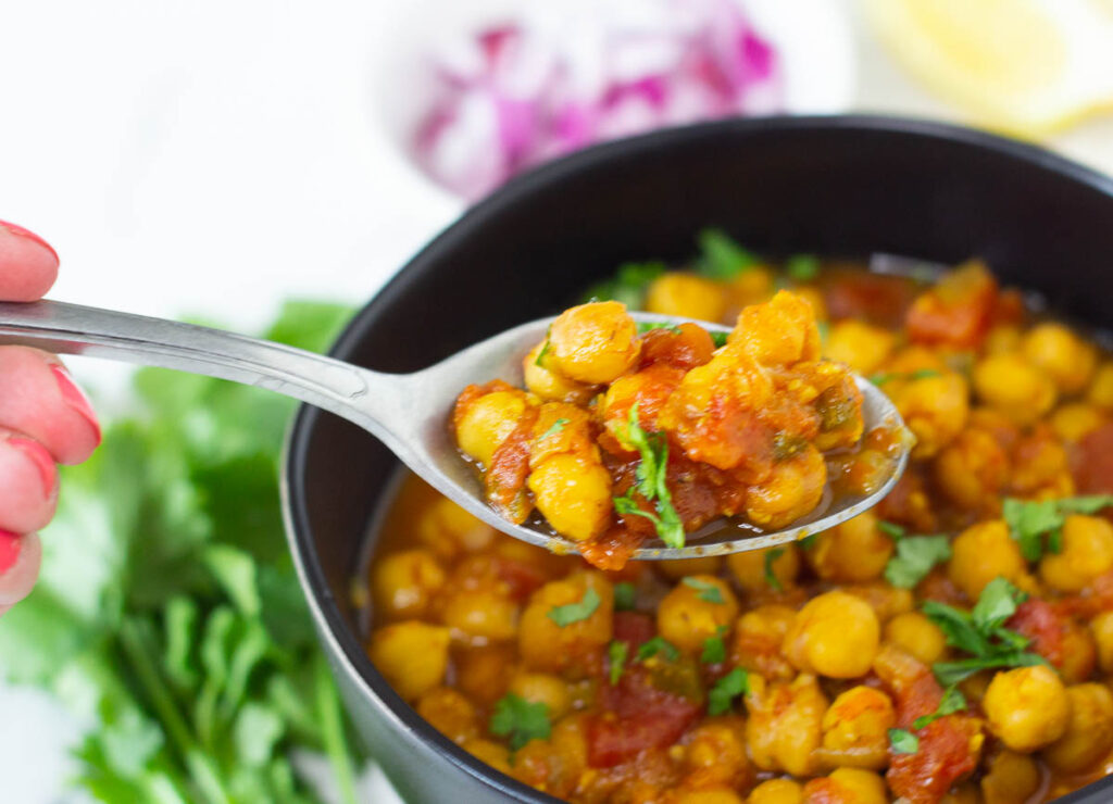 Spoon of spiced chickpeas lifted out of bowl.