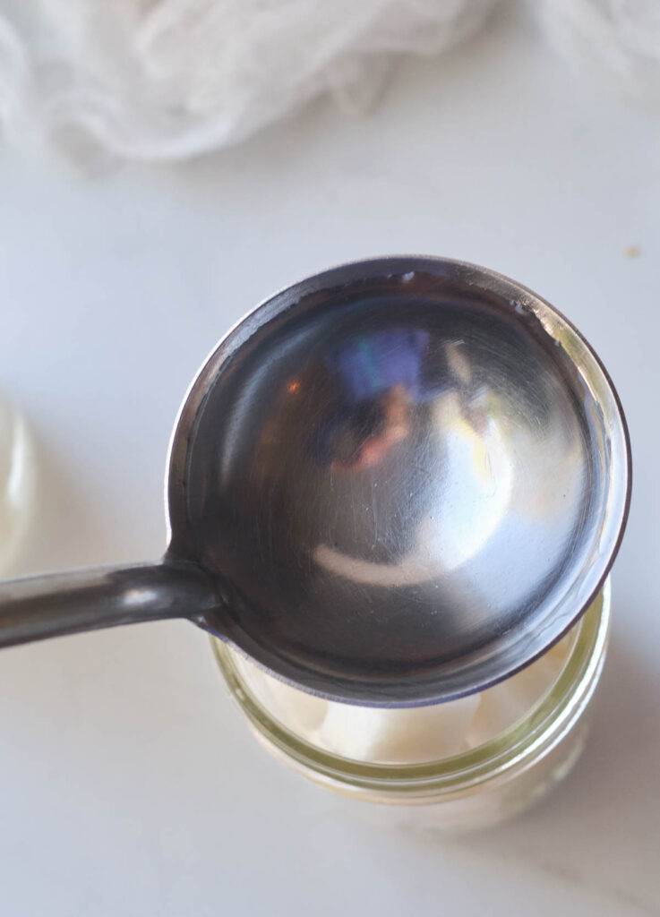 Pouring pickling liquid into mason jar.
