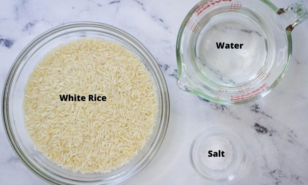 White rice in glass bowl, water in Pyrex measuring cup, and salt in small glass bowl.