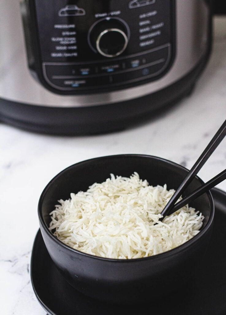 Long grain Ninja foodi rice in black bowl with chopsticks, with Ninja Foodi in background.