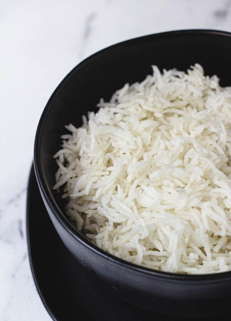 Long grain white rice in black bowl.