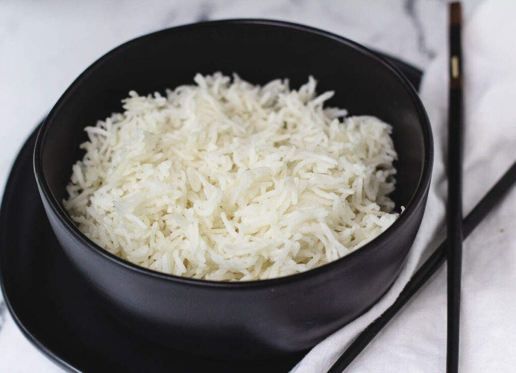 White rice in black bowl on top of black plate paired with a white napkin and chopsticks.