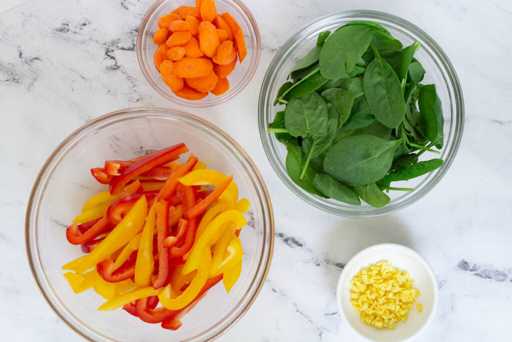 Chopped carrots, leaf spinach, minced ginger, and chopped red and yellow peppers in bowls.