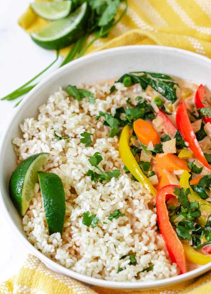Red, and yellow peppers, carrots, and spinach, served with rice and two wedges of lime.