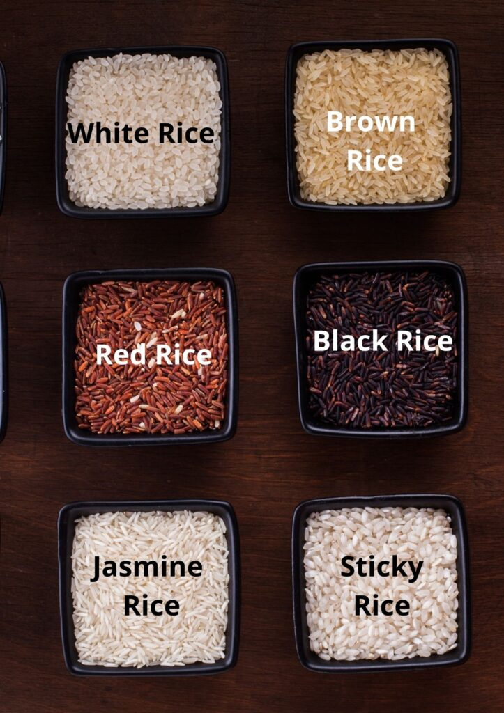 Different types of rice in small square black bowls including white rice, brown rice, red rice, black rice, jasmine rice, and sticky rice.