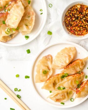 Vegan dumplings on white plate served beside dipping sauce and chopsticks.