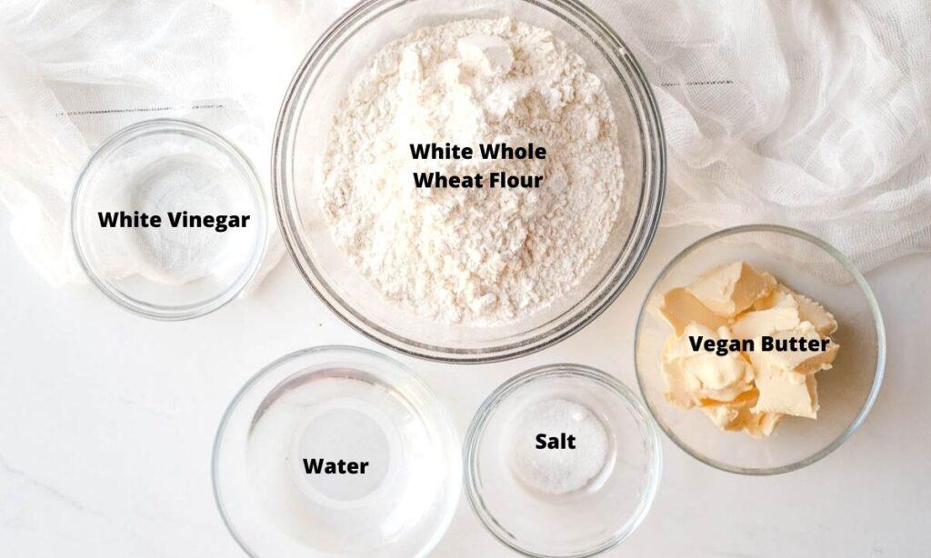 White flour, vegan butter, salt, water, and white vinegar in small bowls.