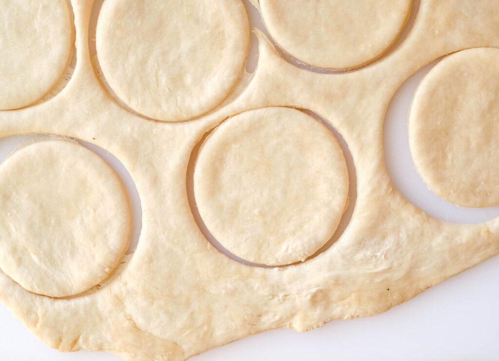 Four inch circles of dough cut out of dough.