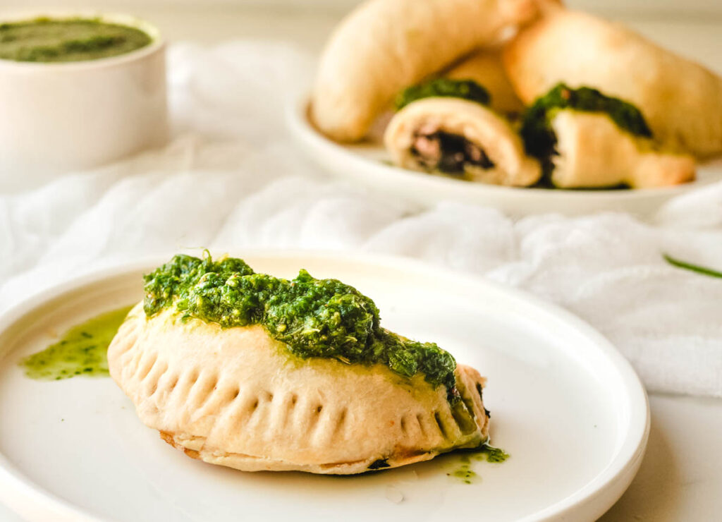 Empanada on white plate topped with green salsa, with other black bean empanadas in the background.