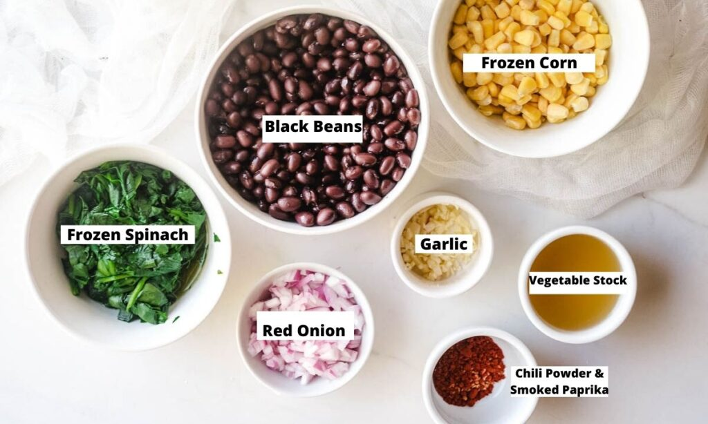 Black beans, frozen corn, frozen spinach, red onion, garlic, vegetable stock, chili powder, and paprika in small bowls.