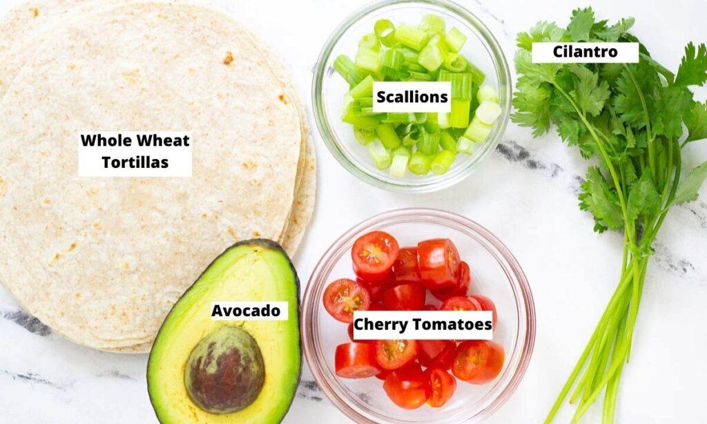 Vegan taco toppings: whole wheat tortillas, scallions, cilantro, cherry tomatoes, and avocado.
