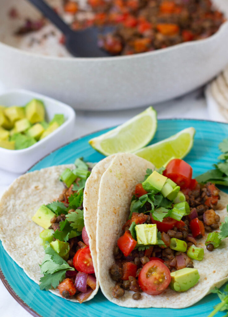 Vegan tacos filled with lentils diced avocado, diced tomato, and scallions.