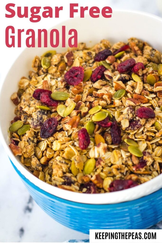 Healthy granola with cranberries, pumpkin seeds, and chopped in nuts, in white and blue bowls stacked together.