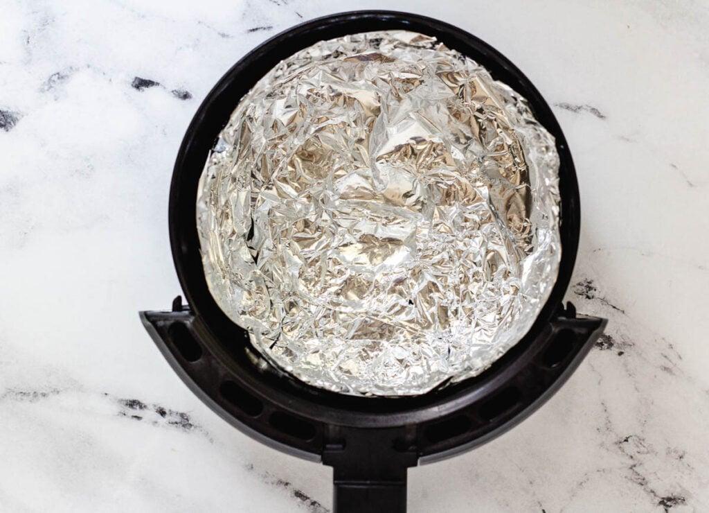 Air fryer basket lined with aluminum foil.