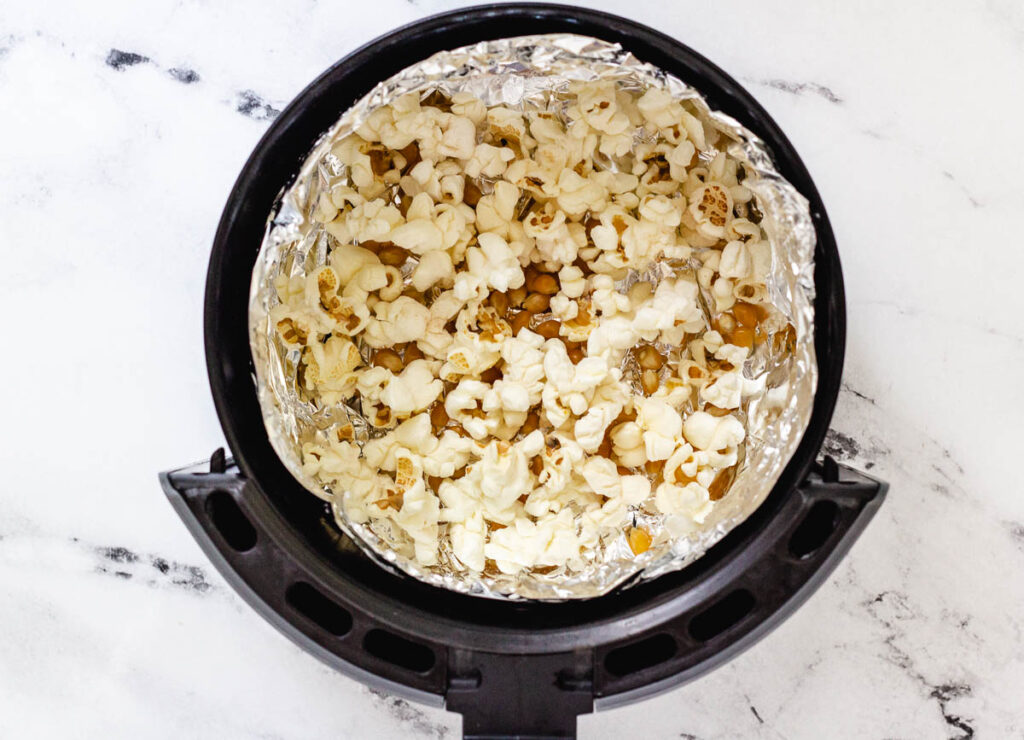 Popped and un-popped corn kernels in air fryer basket lined with aluminum foil.