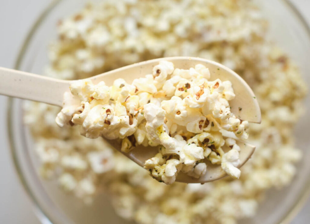 Popcorn on spoon lifted from bowl.