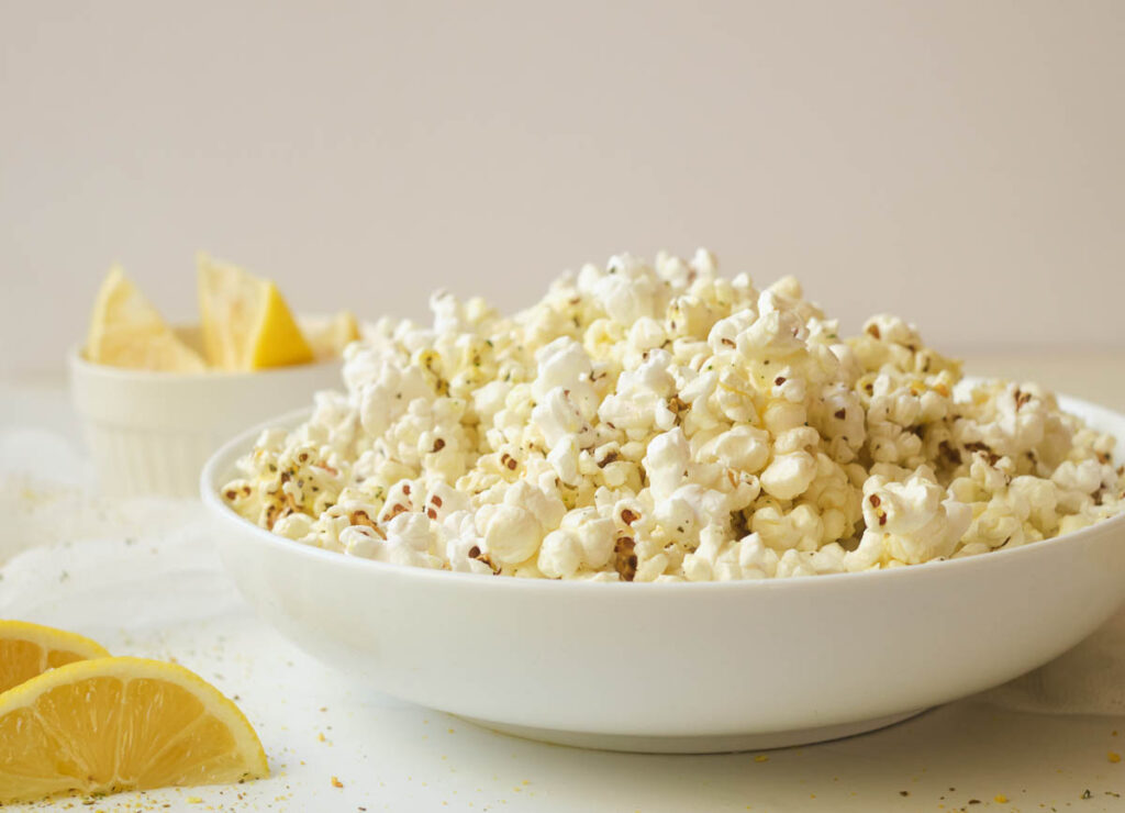 Popcorn in shallow white bowl with wedges of lemon in the background.