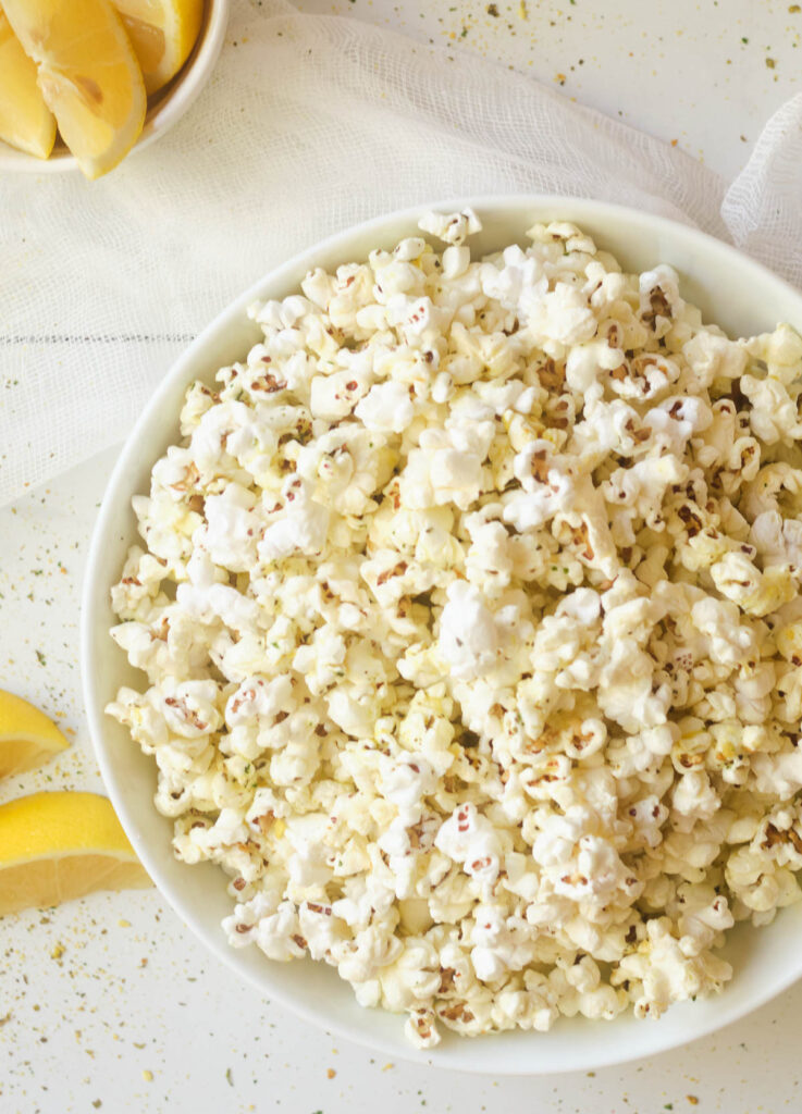 Popcorn in white bowl with lemon wedges beside it.