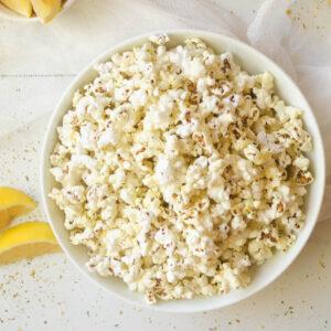 Air fryer popcorn in white bowl.