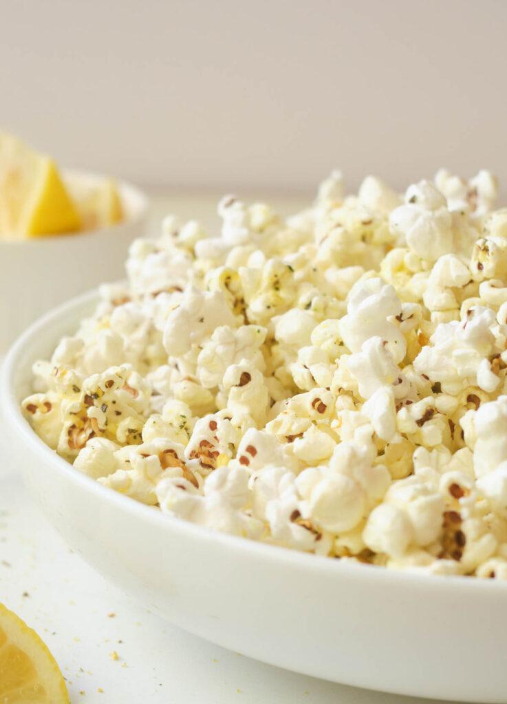 Popcorn in white shallow white bowl.