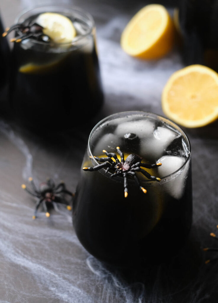 Black widow cocktail in stemless wine glass garnished with lemon and a plastic spider.