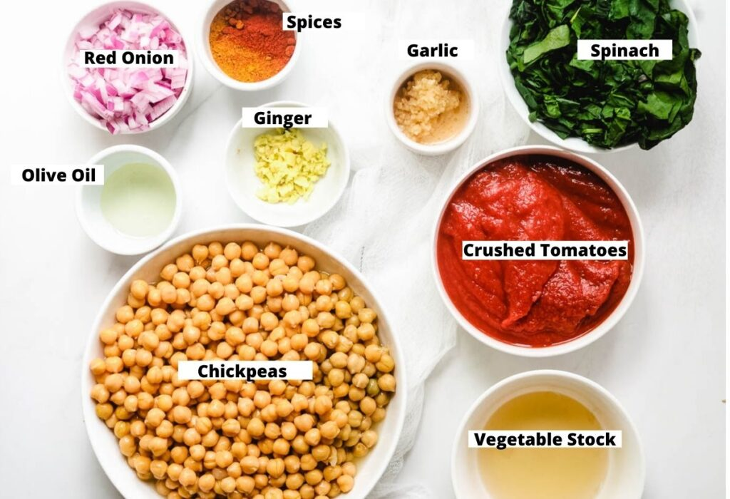 Ingredients for chickpea spinach curry: spinach, crushed tomatoes, vegetable stock, chickpeas, ginger, olive oil, garlic, spices, red onion.
