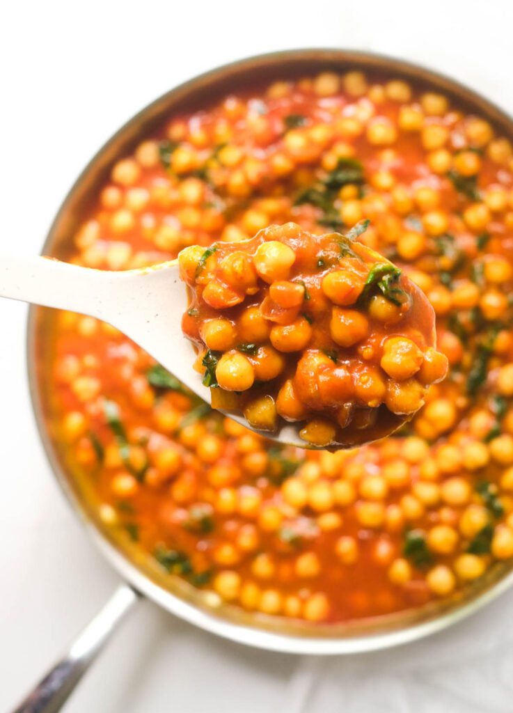 Spoon lifting chickpea curry from pot.