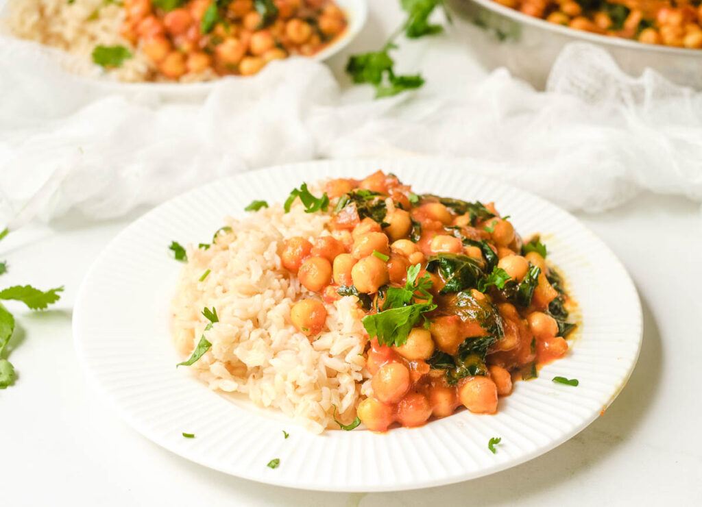 Chickpea curry spinach on white plate served with brown rice.