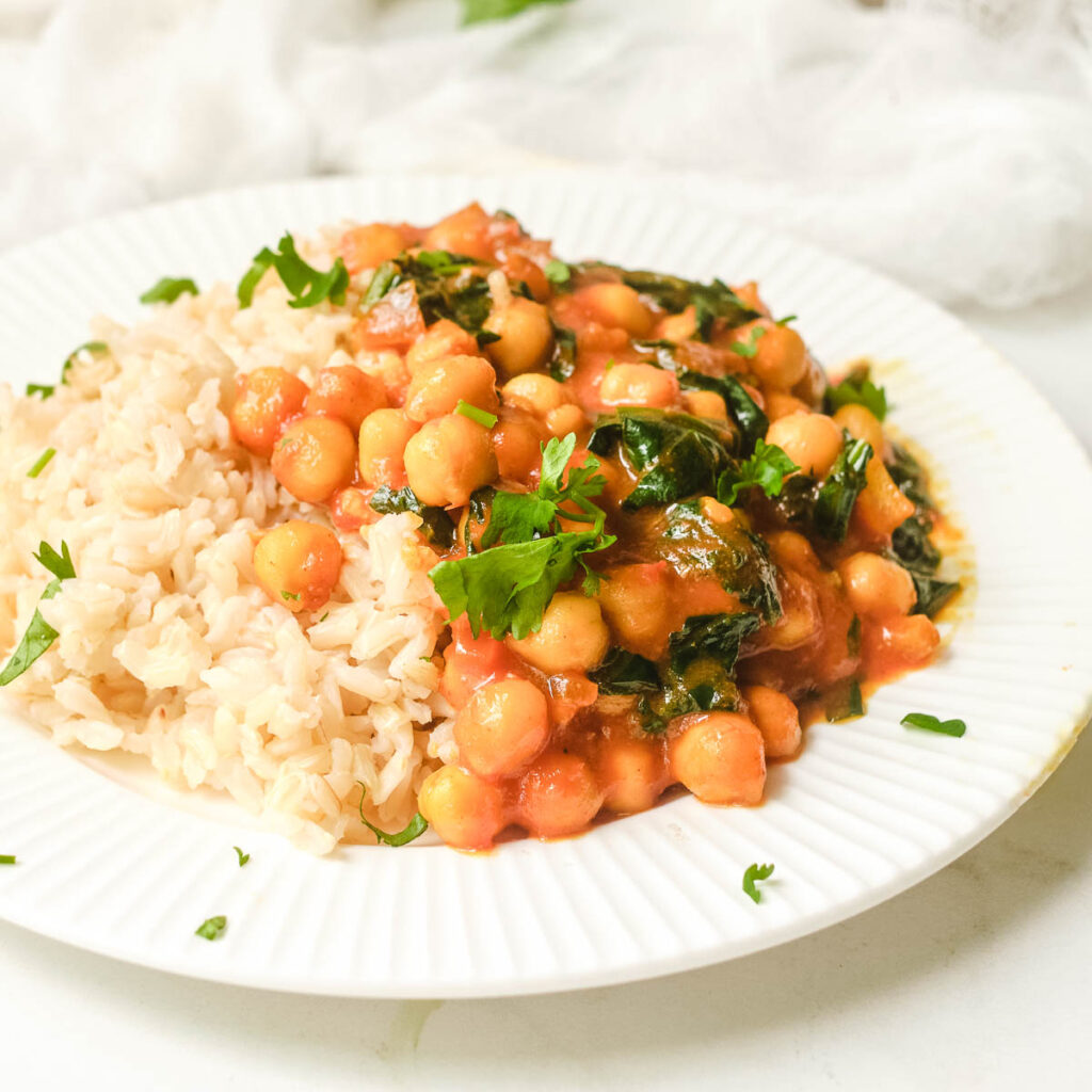Chickpea spinach curry served on white plate with rice, and garnished with cilantro.