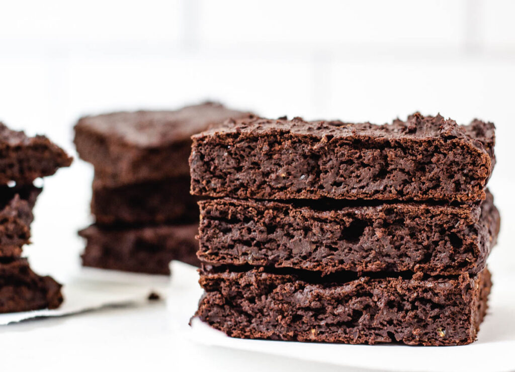 Stack of three fudgy brownies with other stacks of brownies in the background.