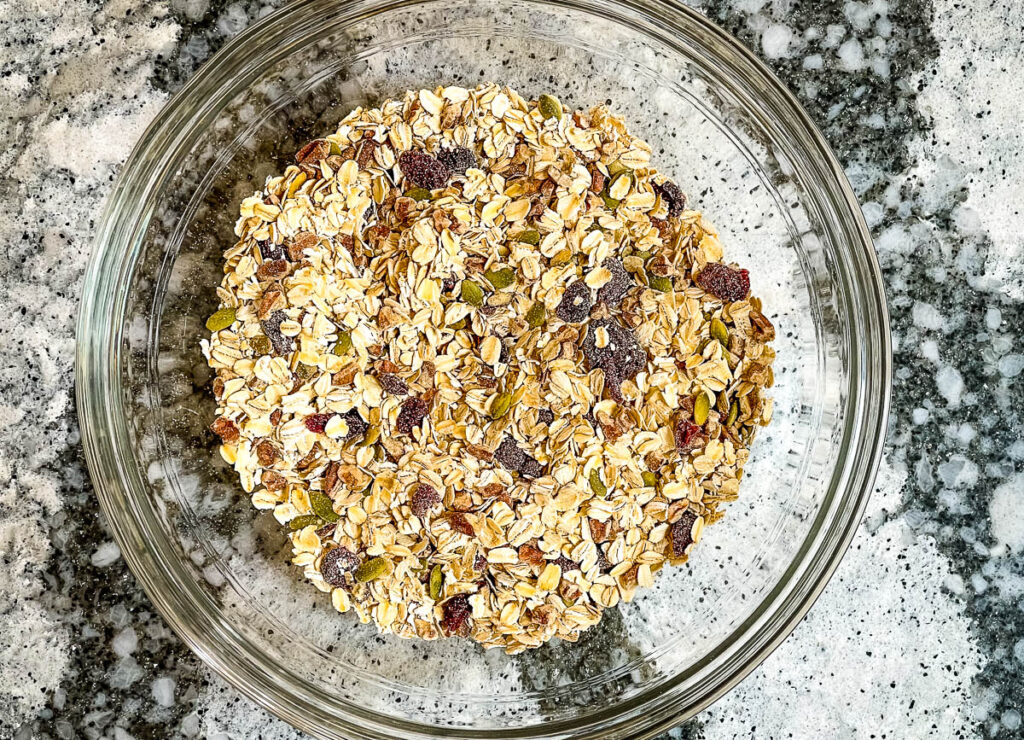 Oats, pumpkin seeds, pecans, and cranberries in glass bowl.