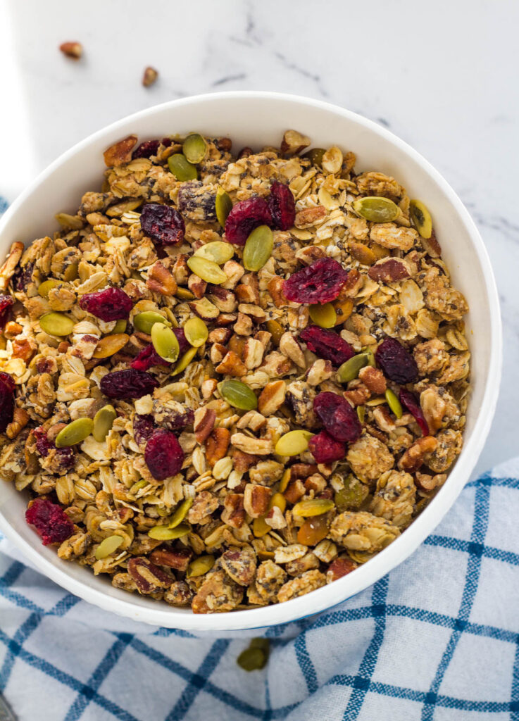 Cranberry, pumpkin seed granola in white bowl.