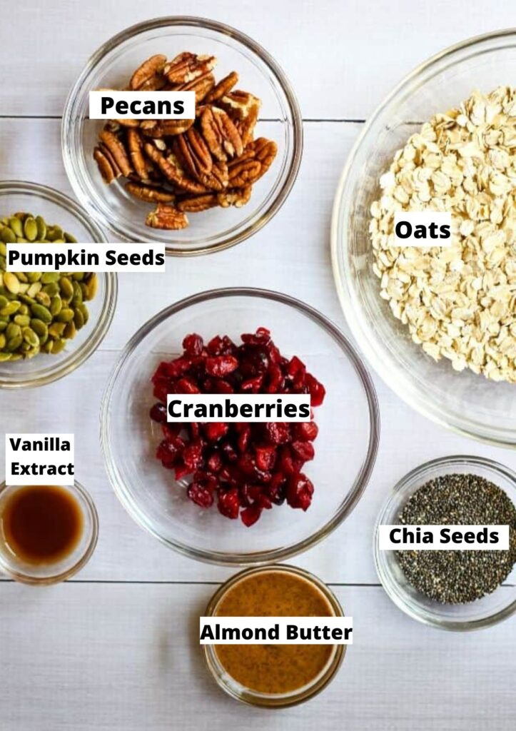 Ingredients for sugar free granola in glass bowls: pecans, oats, pumpkin seeds, cranberries, vanilla extract, almond butter, and chia seeds.