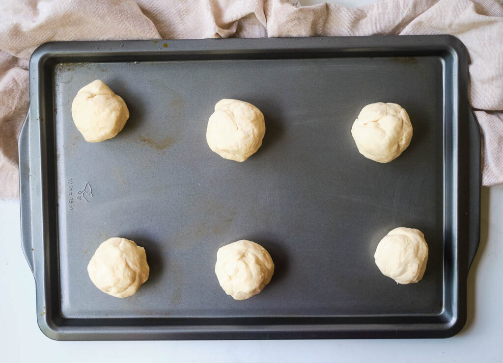 Six balls of dough on baking sheet.