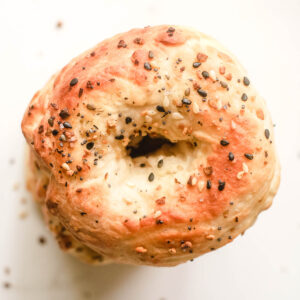 Vegan bagel topped with sesame seeds and poppy seeds.
