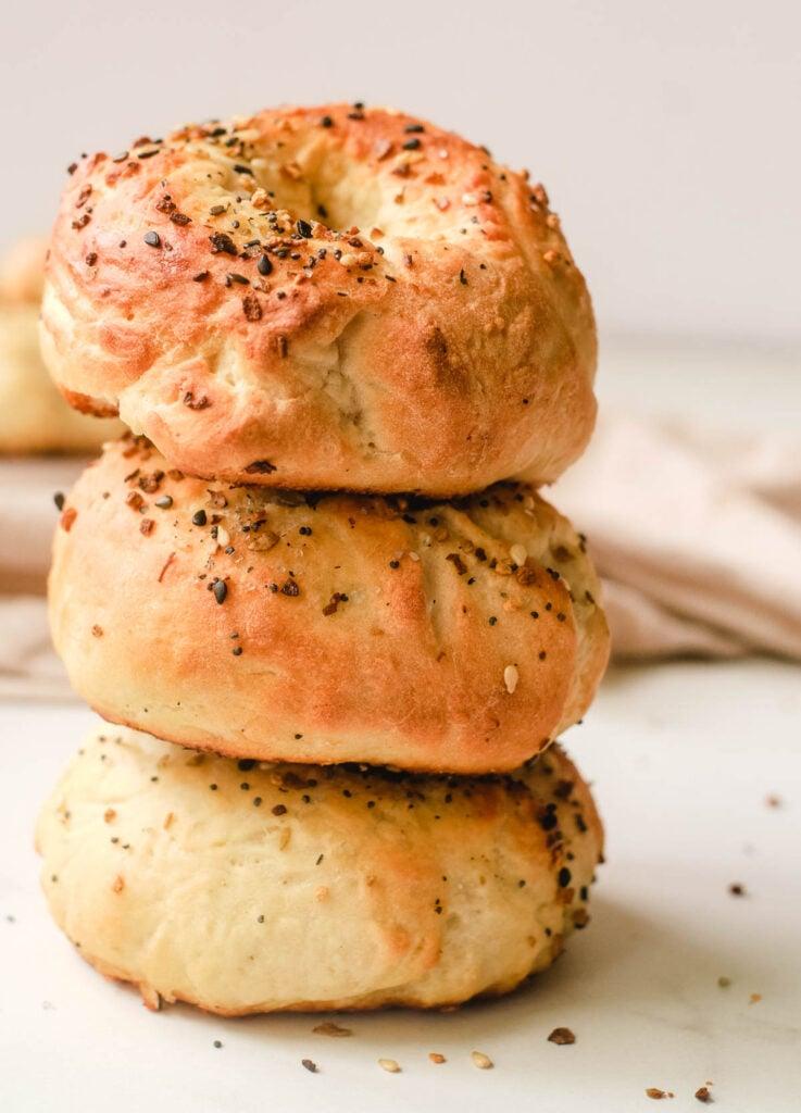 Stack of three vegan bagels topped with everything seasoning.