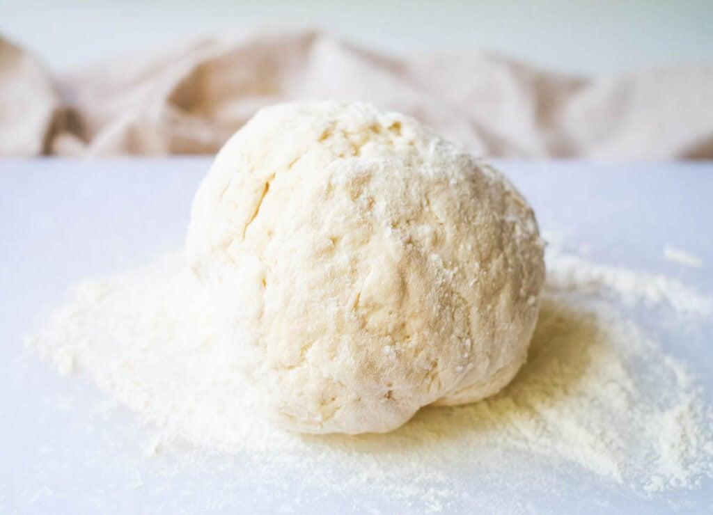 Ball of dough on floured surface.