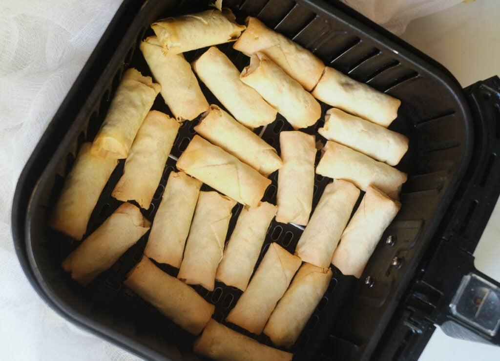 Frozen spring rolls in air fryer basket.