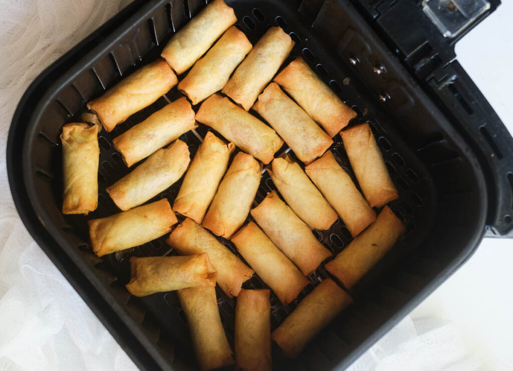 Cooked frozen spring rolls in air fryer basket.