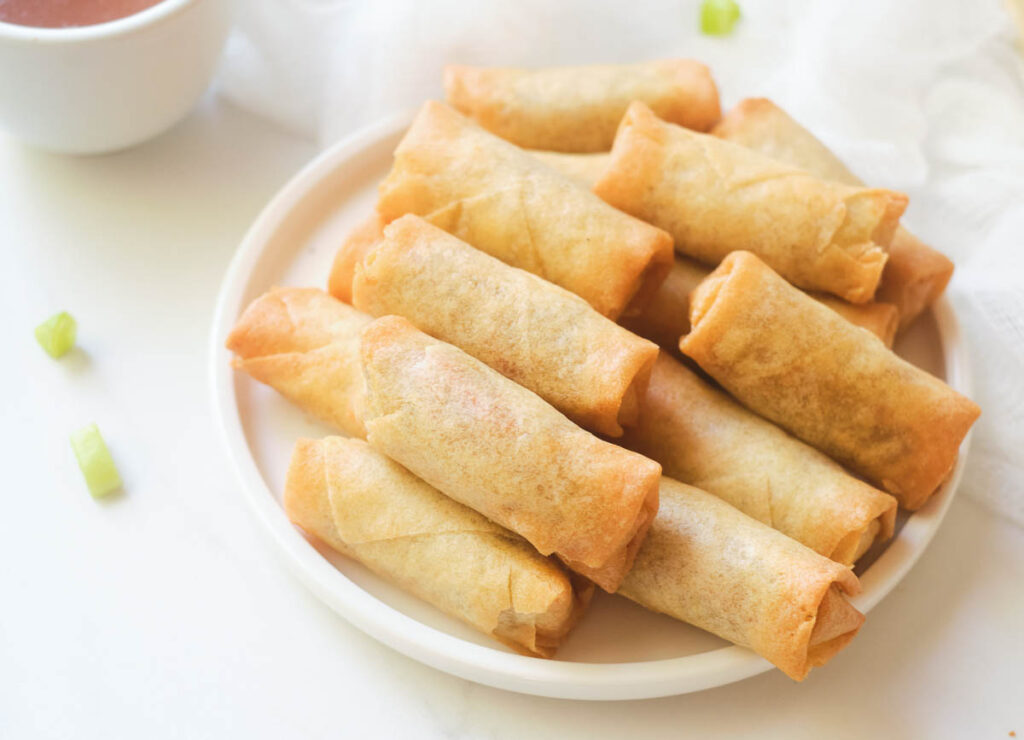 Cooked golden brown spring rolls on white plate.