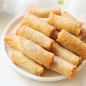 Cooked air fryer frozen spring rolls stacked on white plate.
