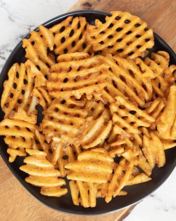 Air fryer waffle fries on black plate.
