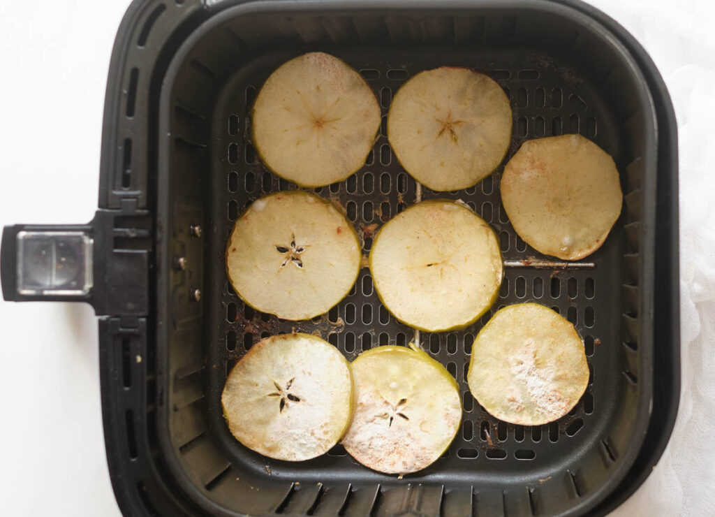 Thinly sliced and cooked apple rounds in the air fryer basket.