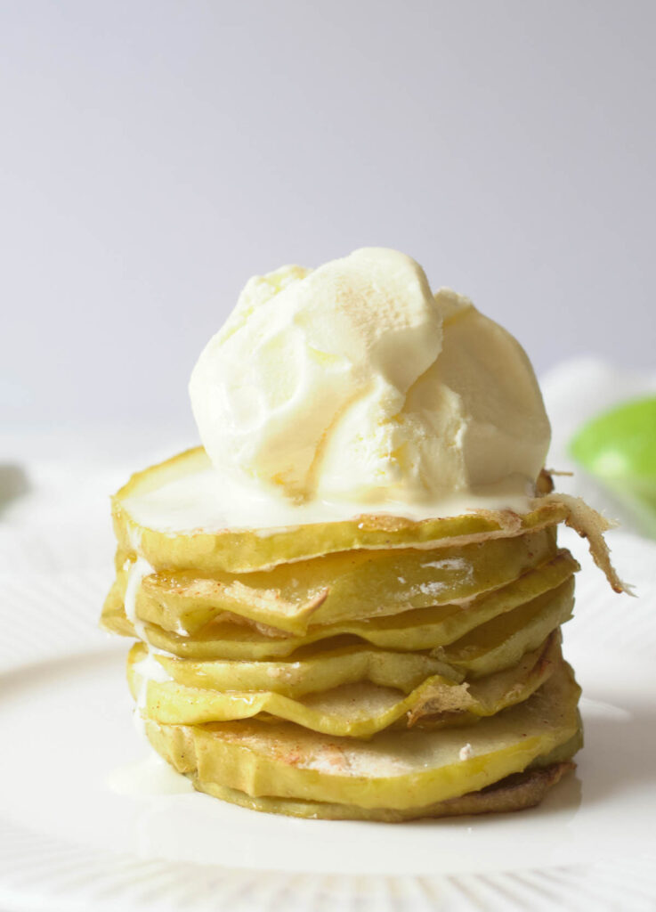 Stack of apple chips topped with vanilla ice cream.