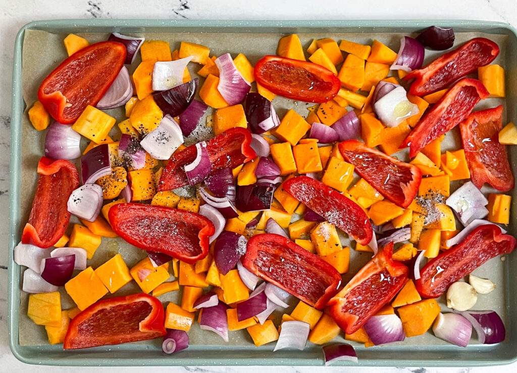 Diced butternut squash, red pepper slices, red onion chunks, garlic cloves, drizzled with olive oil, and topped with salt and pepper on roasting pan.