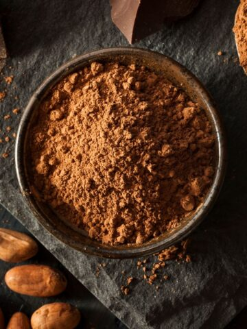 Cocoa powder in black bowl surrounded by cocoa beans and chocolate.